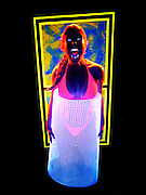 Screaming woman with glowing bikini holding glowing mesh against a glowing yellow frame.Black light