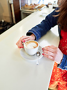 Faceless shot of stylish woman sitting at table with cup of freshly made latte in cafeteria of Rome.