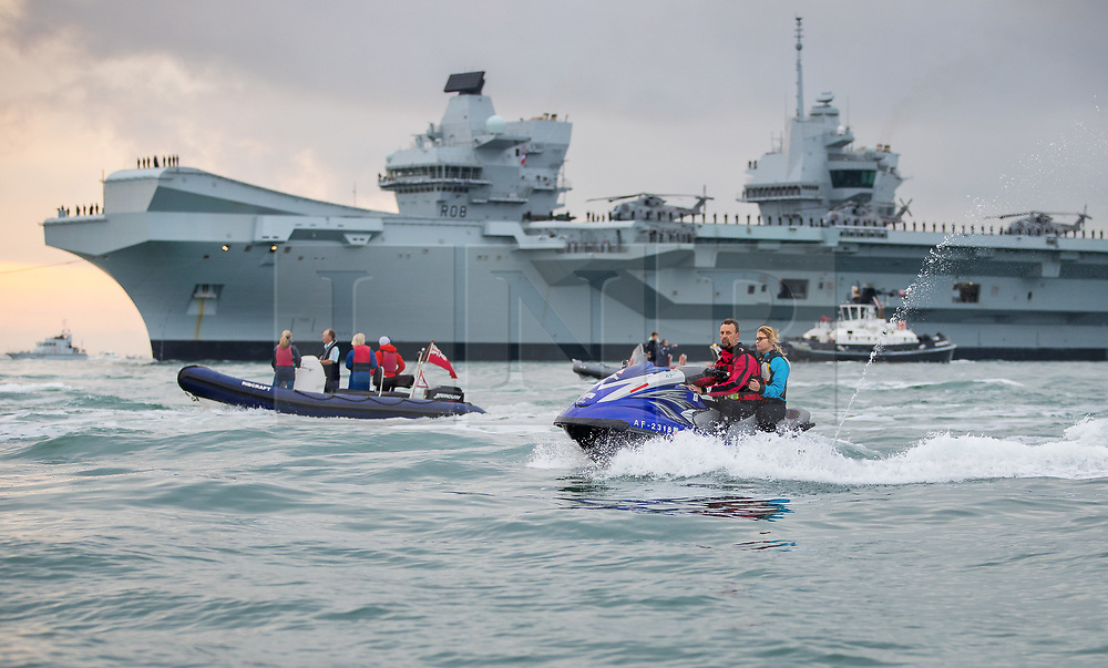 © Licensed to London News Pictures. 16/08/2017. Portsmouth, UK. A flotilla of small boats and a couple on a jet ski follows the Royal Navy's new aircraft carrier HMS Queen Elizabeth as she enters her home port of Portsmouth for the first time. The new ship at 65,000 tonnes is the biggest warship ever built in the UK. Photo credit: Peter Macdiarmid/LNP