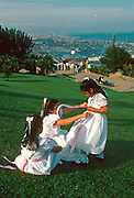 SPAIN, CATALONIA, BARCELONA Montjuich Park and harbor children playing after first communion