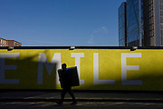 A man carries an awkward square box past a large yellow sign with spelling the word Mile.