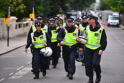 © Licensed to London News Pictures. 29/08/2016. London, UK. Police in riot gear watch over as Carnival goers enjoy day two of the Notting Hill carnival, the second largest street festival in the world after the Rio Carnival in Brazil, attracting over 1 million people to the streets of West London.  Photo credit: Ben Cawthra/LNP