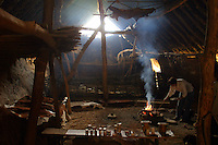 Cooking in a Neolithic hut reconstuction built from wood, daub & thatch at L'Archeodrome de Bourgogne.
