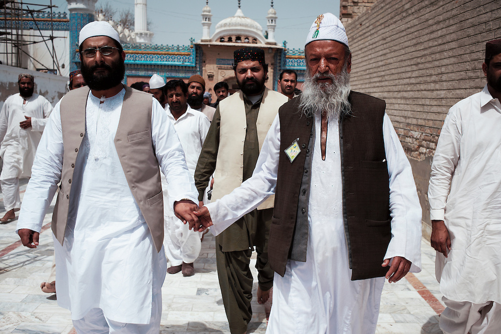 Faqir Muhamad Abdul Hai alias Mian Shaman(right) waits for prayer time at Bharchundi Sharif, a Muslim shrine in Ghotki district, Sindh, Pakistan on March 23, 2012. Mian Shaman was the religious leader who converted a Hindu girl Rinkle Kumari to Islam.  A rise in in reports of forced conversion of Hindu girls to Islam in provinces in Pakistan has gained prominence within the political, media, religious and social domains with the case of a 21 year old woman Rinkle Kumari. On February 24, 2012 her family reported to police of Ghotki district, Sindh province that she had been abducted by armed men from the family home in the village of Mirpur Mathelo. it is then alleged by the family and broadrer hindu community that she was forced to convert to Islam and marry Syed Naveed Shah, a neighbour of the girl within their village. Complications with court hearings for the case, perceptions by the Muslim community that the police sided with the Muslim community when dealing with issue and the politicisation of the case by a Pakistan Peoples Party Member for National Assembly Mian Abdul Haq alias Mian Mitho has led to a hearing being called in the Supreme Court, Islamabad, Pakistan on March 26, 2012. The hearing will hopefully ascertain whether the girl was abducted or in fact left with Syed Naveed Shah of her own free will.