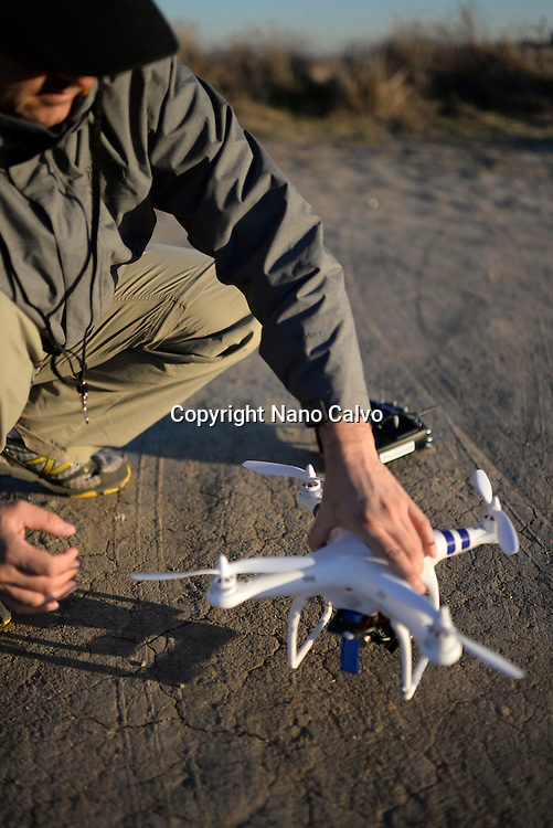 Young man flying a quadcopter DJI phantom drone outdoors