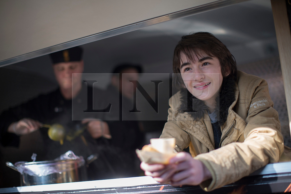 © licensed to London News Pictures. London, UK 04/03/2013. Isaac Hempstead Wright, who plays Bran Stark in Game of Thrones HBO show, handing out food to fans as he helps to promote show's Season 2 DVD launch with Game of Thrones food wagon in central London. Photo credit: Tolga Akmen/LNP
