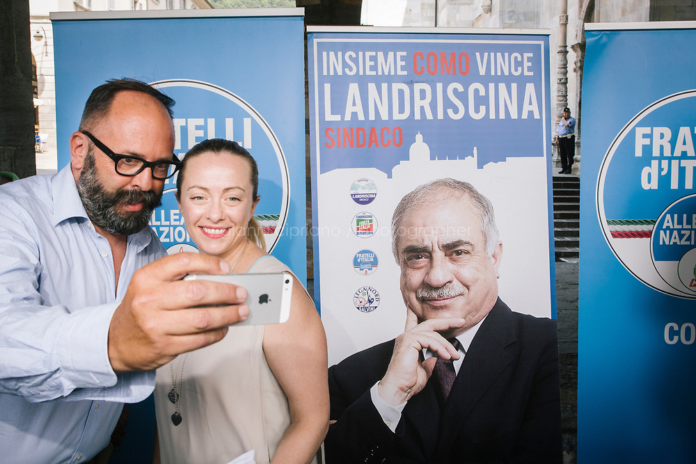 COMO, ITALY - 21 JUNE 2017: Giorgia Meloni (right), leader of the Fratelli d&rsquo;Italia party, takes a selfie with a supporter at the end of Mr Landriscina's rally in Como, Italy, on June 21st 2017.<br /> <br /> Residents of Como are worried that funds redirected to migrants deprived the town&rsquo;s handicapped of services and complained that any protest prompted accusations of racism.<br /> <br /> Throughout Italy, run-off mayoral elections on Sunday will be considered bellwethers for upcoming national elections and immigration has again emerged as a burning issue.<br /> <br /> Italy has registered more than 70,000 migrants this year, 27 percent more than it did by this time in 2016, when a record 181,000 migrants arrived. Waves of migrants continue to make the perilous, and often fatal, crossing to southern Italy from Africa, South Asia and the Middle East, seeing Italy as the gateway to Europe.<br /> <br /> While migrants spoke of their appreciation of Italy&rsquo;s humanitarian efforts to save them from the Mediterranean Sea, they also expressed exhaustion with the country&rsquo;s intricate web of permits and papers and European rules that required them to stay in the country that first documented them.