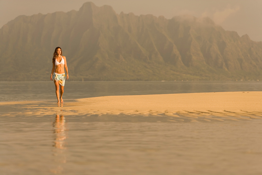female walking exposed sand bar in Kaneohe Bay, Koolau Mountains at Kualoa as backdrop.