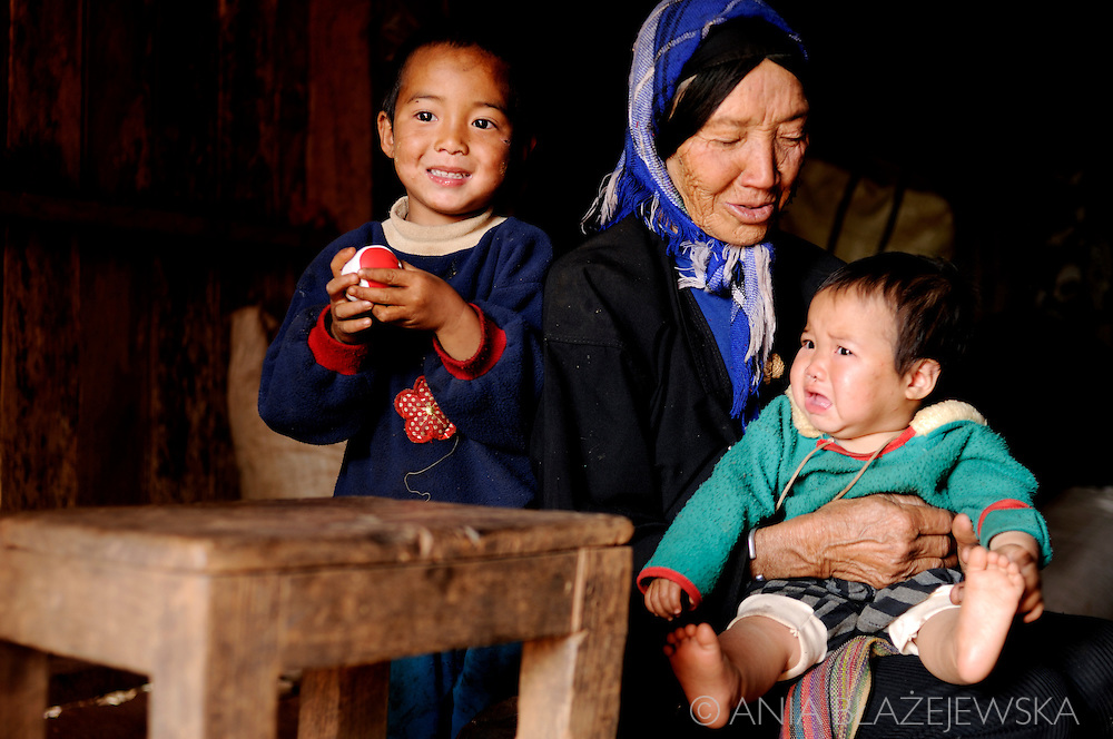 Burma/Myanmar. Family scene from Akha tribe: grandmother, boy and a crying baby.