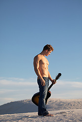 shirtless muscular lean man with a guitar on a sand dune