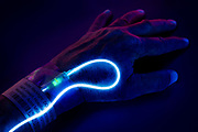 A glowing IV on a wrist with a hospital ID band. Blacklight Photography.