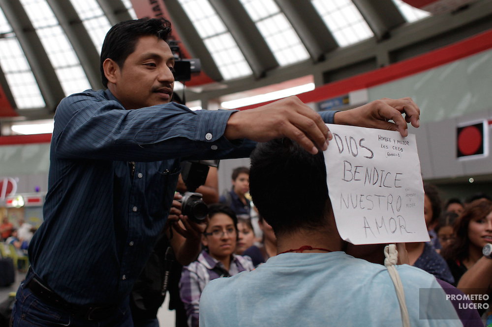 """A religious man reacts as a male couple kisses putting a banner that reads """"God bless our love"""" (referring him ans his wife). .Lesbian and homosexual couples and activists joined in the Eastern Bus Passengers Station (Terminal de Autobuses de Pasajeros de Oriente) to perform the """"Besaton"""" (group kiss) in Mexico City on May 17th, 2012. The Besaton, a protest in the International Day against Homophobia is made after a female couple was expelled by policemen and private security from the place on May 13th.. (Photo: Prometeo Lucero)"""