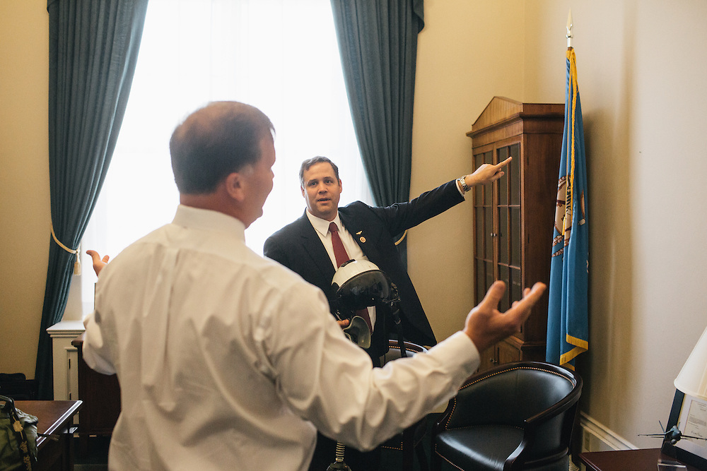 Congressman Jim Bridenstine looks for places to hang his old flight gear given to him by his former squadron mate Ben Sale, left, before heading to the Capitol for a vote on Sept. 19, 2013.