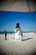 A man on his cell phone seems unfazed by the snow man on Treasure Island Beach in Florida December 18, 2011.<br />