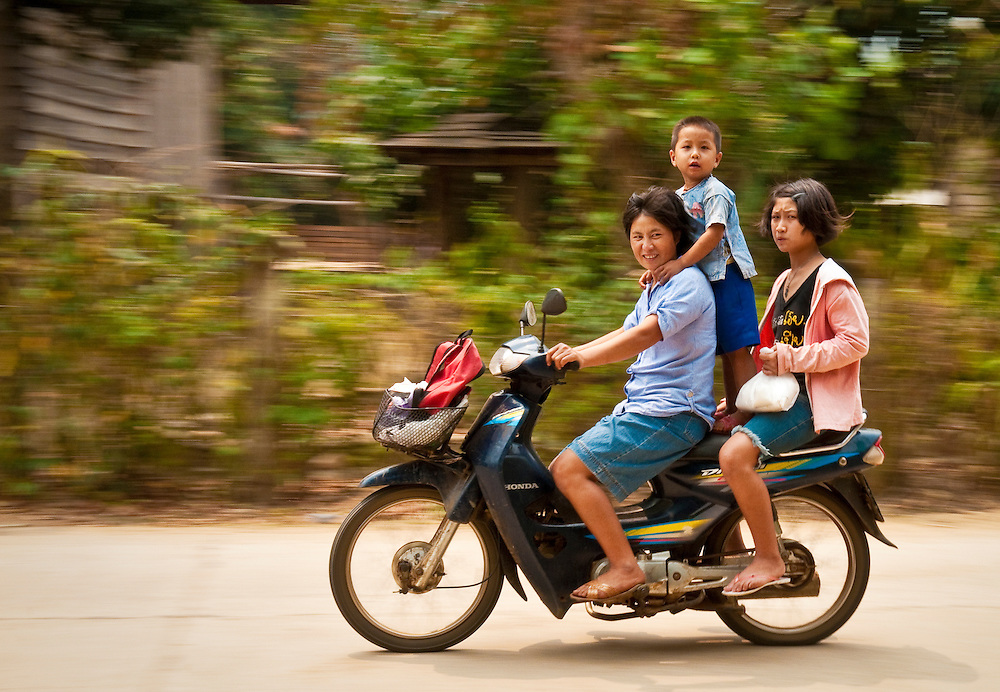 Family riding motorcycle through village along the Mae Taeng River in rural Chiang Mai Province, Thailand.