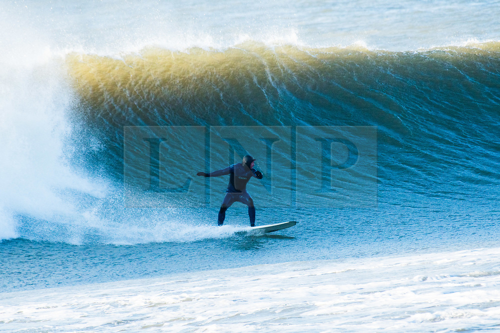 © Licensed to London News Pictures. 14/12/2018. Aberystwyth, UK.  Brave and hardy surfers make the most of the huge surf waves  rolling in off the Atlantic on a sunny but bitterly cold, cold and windy day in Aberystwyth Wales. <br /> Photo credit: Keith Morris/LNP