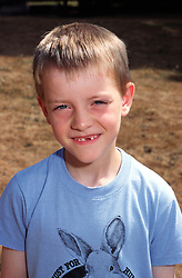 Portrait of young boy with missing teeth smiling,
