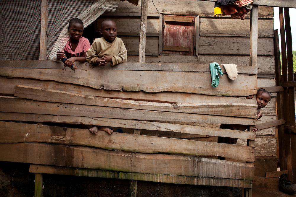 Kids in Carriere, a poor area of Yaounde where most of the houses are built with wood by the residents. people here are scared to draw attention to themselves, because the mayor has been dealing with slums by simple tearing them down, leaving people homeless. Yaounde, Cameroon.