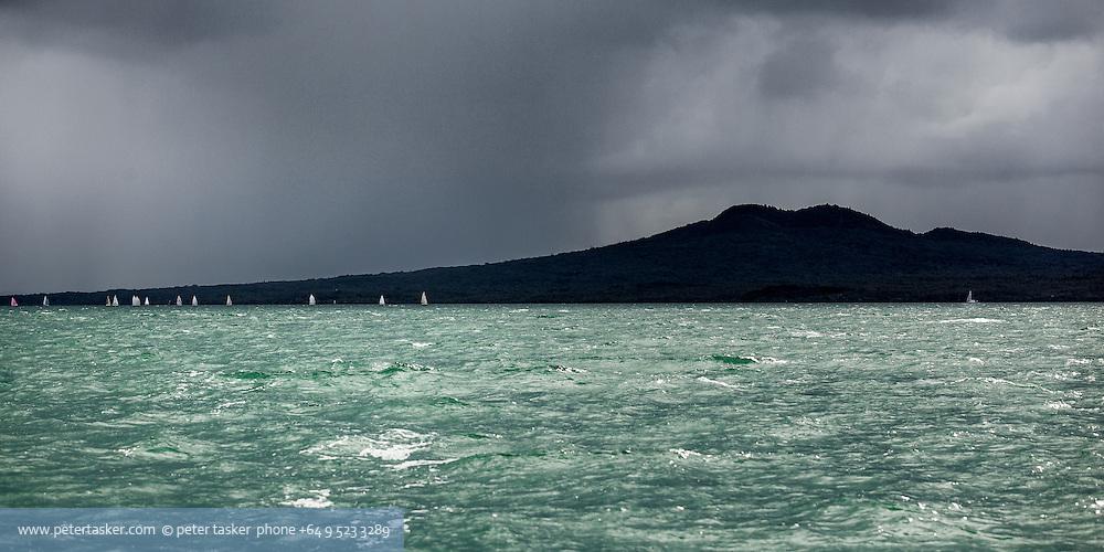 A rainy day yacht race progessing along the coast of Rangitoto Island.
