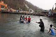 One of many photographers<br /> that wander the bathing area,<br /> giving the swimmers instructions<br /> to take their picture. Shwet Set<br /> Taw, Magwai Division, Myanmar.<br /> February 2014.