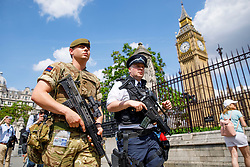 © Licensed to London News Pictures. 24/05/2017. London, UK. An armed soldier and armed police officer patrol around the Houses of Parliament in Westminster, London on Wednesday, 24 May 2017 after the Manchester Arena bombing. As the terrorism threat level has been raised to critical and Operation Temperer has been deployed and 5,000 troops are taking over patrol duties under police command. Photo credit: Tolga Akmen/LNP