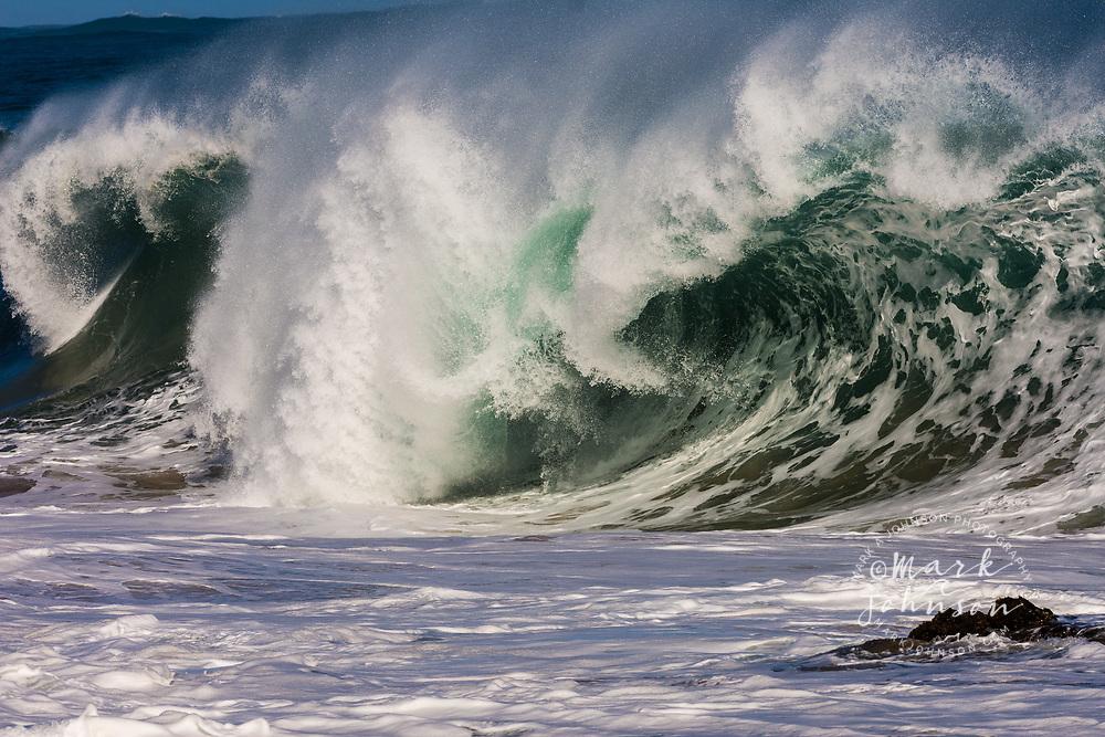 A powerful wave breaking off of a beach on Kauai, Hawaii