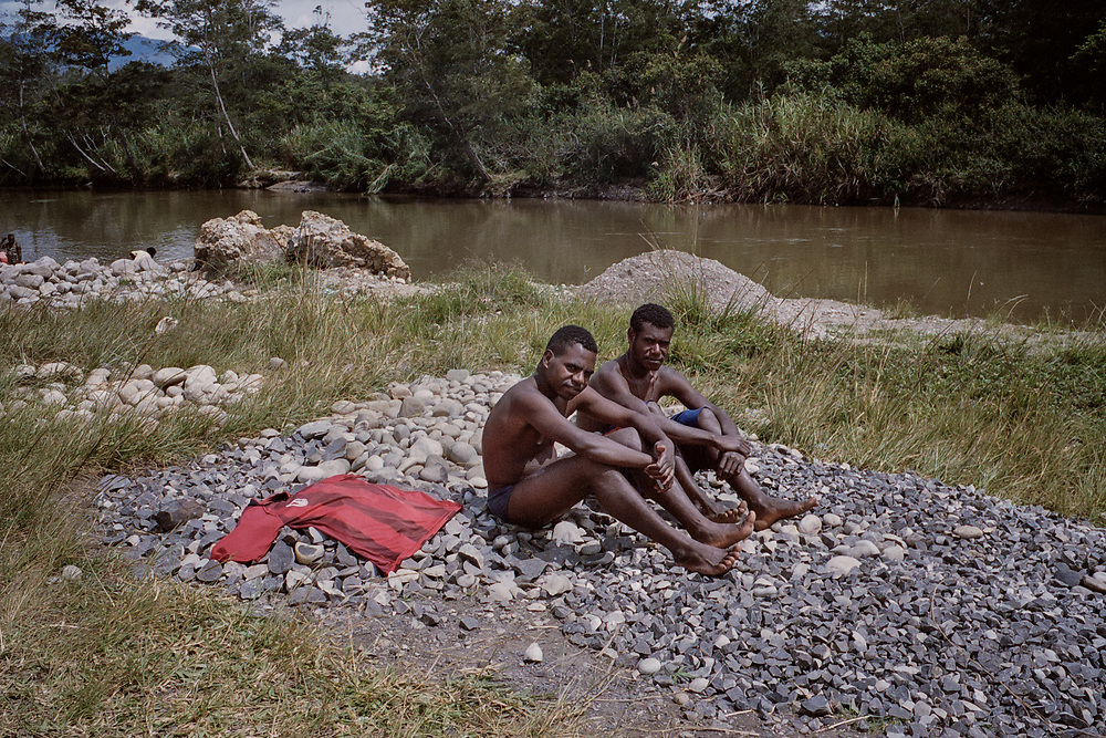 Young men drying after bathing in Wouma river in Wamena.<br /> <br /> Scenery (establishing shots)