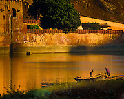 Fishermen working along the waterbanks outside the Amber Fort,  just after sunrise in Jaipur, India. <br /> <br /> Nikon D750 300mm  ISO 1600  f11  1/3200s