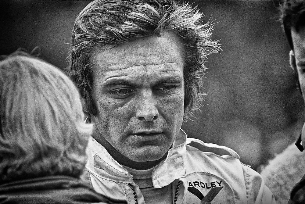 American Peter Revson, seen here during practice for the 1972 United States Grand Prix, seemed to have positioned himself for F1 stardom by the fall of that year. He had surprised everyone with his pole position and 2nd place finish at the Indianapolis 500 in 1971, and went on to also capture that year's Can-Am Championship, both times driving for McLaren. <br /> <br /> It was Revson's bad fortune to be linked to a grand fortune...his family was related to the Revlon company, and although he didn't share directly in that wealth, he had to bear the label &quot;playboy racer.&quot;<br /> <br /> Instead, his rise to racing's highest level was managed with great heartache. He lost his best friend and racing partner, Timmy Mayer, while barnstorming Europe in Formula Junior, and his younger brother Doug, in a Formula 3 race in Denmark. <br /> <br /> He had a victory in the 1965 Monaco F3 race in his pocket, but didn't get any offers for race seats until devoting his career to the United States Can-Am series in 1966. He was finally able to demonstrate his abilities and was signed by McLaren in 1971. He promptly won the championship.<br /> <br /> He won the 1973 British and Canadian Grands Prix for McLaren, but was replaced in 1974 by former World Champion Emerson Fittipaldi. He found a home with Shadow that season, but was killed in March during testing for the South African Grand Prix when his front suspension failed.