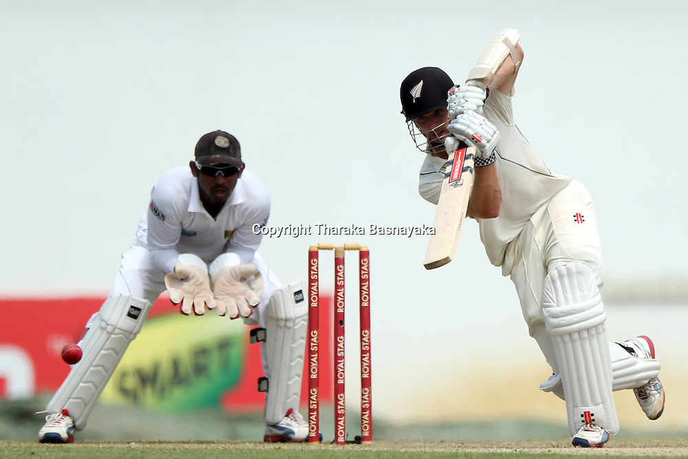 New Zealand cricketer Kane Williamson (R) is watched by Sri Lankan wicketkeeper Prasanna Jayawardene as he plays a shot during the first day of the second and final Test match between Sri Lanka and New Zealand at the P. Sara Oval Cricket Stadium in Colombo on November 25, 2012. New Zealand captain Ross Taylor won the toss and elected to bat.