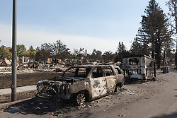 A burned out car and trailer sit on the side of a street in the destroyed neighborhood of Coffey Park, in Santa Rosa, California.