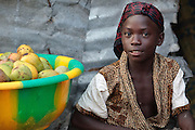 A girl sits next to a plastic container filled with mangoes in the West Point slum in Monrovia, Montserrado county, Liberia on Monday April 2, 2012.