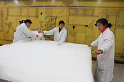 China, Beijing, Silk factory visitor Center, Female workers stretching sheets of silk