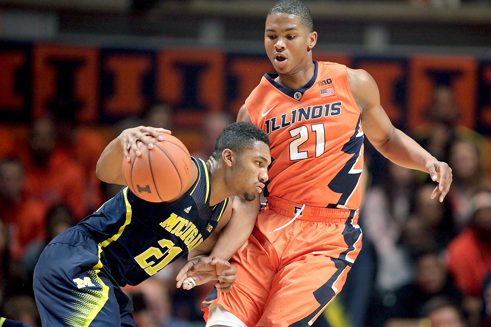 Illinois guard Malcolm Hill (21) defends against Michigan guard/forward Zak Irvin (21) during overtime of an NCAA college basketball game at the State Farm Center Thursday, Feb. 12, 2015, on the University of Illinois campus in Champaign, Ill. Illinois won the game 64-52. (For the Herald & Review/ Stephen Haas)