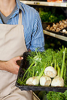 Midsection of man holding basket of green onion in supermarket