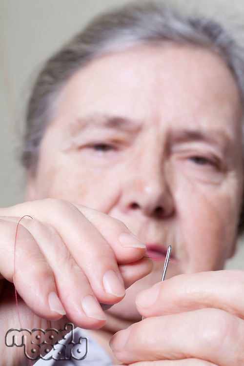 Elderly lady threads a needle
