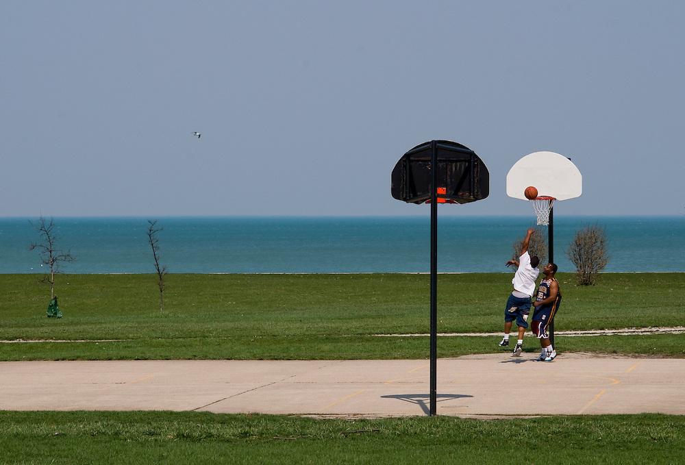 Two friends playing basketball at a court along the Chicago Lakefront Trail.<br /> <br /> The Chicago Lakefront Trail is an 18-mile multi-use path in Chicago, Illinois along the coast of Lake Michigan. The path connects various beaches and recreational amenities located along the lake front and also serves as an option to bicycle commuters.<br /> <br /> Green Chicago.Photographer: Chris Maluszynski /MOMENT