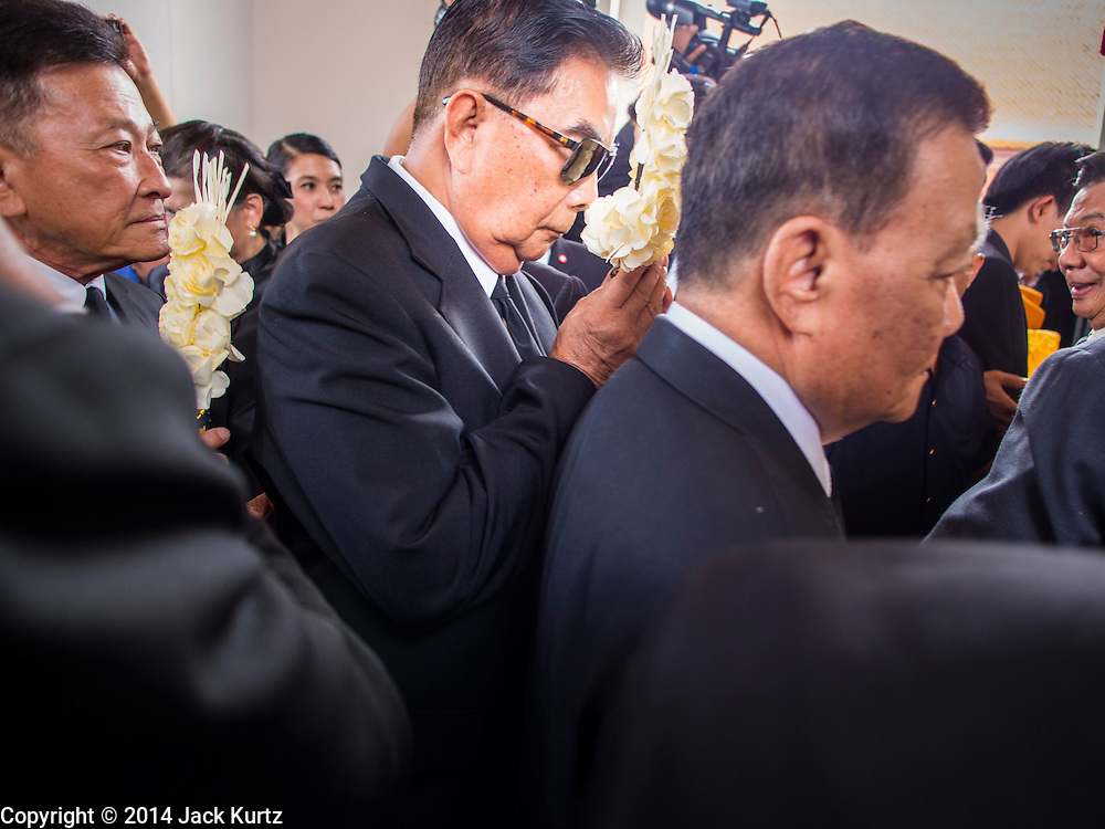 19 OCTOBER 2014 - BANG BUA THONG, NONTHABURI, THAILAND: Mourners file into the crematorium to leave flowers at Apiwan Wiriyachai's cremation at Wat Bang Phai in Bang Bua Thong, a Bangkok suburb, Sunday. Apiwan was a prominent Red Shirt leader. He was member of the Pheu Thai Party of former Prime Minister Yingluck Shinawatra, and a member of the Thai parliament and served as Yingluck's Deputy Prime Minister. The military government that deposed the elected government in May, 2014, charged Apiwan with Lese Majeste for allegedly insulting the Thai Monarchy. Rather than face the charges, Apiwan fled Thailand to the Philippines. He died of a lung infection in the Philippines on Oct. 6. The military government gave his family permission to bring him back to Thailand for the funeral. His cremation was the largest Red Shirt gathering since the coup.     PHOTO BY JACK KURTZ