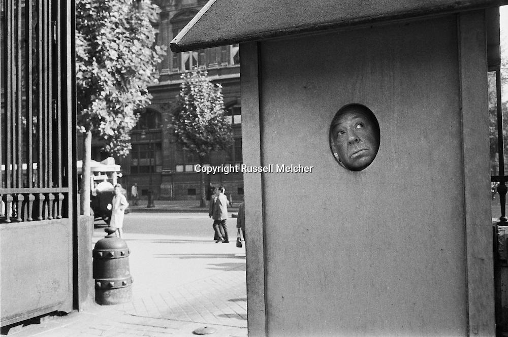 Alfred Hitchcock hamming it up, looking out of the guard box in the Conciergerie in Paris.<br /> <br /> Alfred Hitchcock jouant , regardant hors de la cabine de surveillance de  Conciergerie &agrave; Paris .