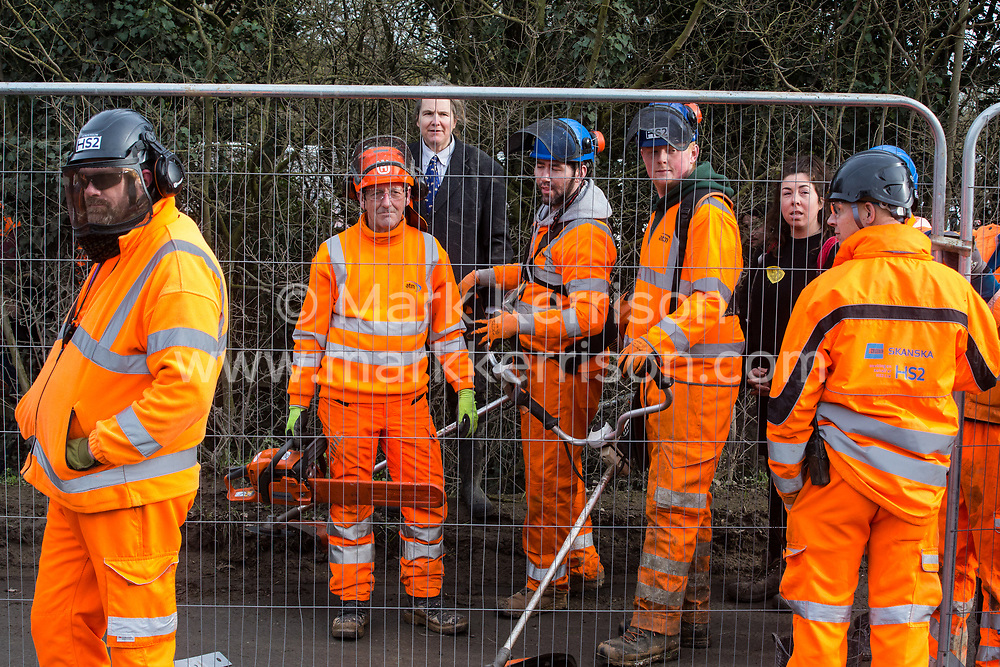 Harefield, UK. 8 February, 2020. Environmental activists seek to prevent HS2 engineers from using a chainsaw and streamers to carry out tree felling works for the high-speed rail project alongside Harvil Road in the Colne Valley. The activists, based at a series of wildlife protection camps in the area, prevented the tree felling, for which road and rail closures had been implemented, for the duration of the weekend for which it had been scheduled.