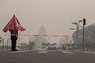 PEQUIM, CHINA, 09h54 (horario local) 26/7/2008: ***EXCLUSIVO FOLHA*** Coberto por forte poluicao , o Estadio Nacional (Ninho de Passaro) e vigiado por soldado do  exercito chines. Obs: o guarda-sol que protegia o jovem soldado do sol de 35 graus centigrados se fechou no instante da foto. (foto: Caio Guatelli/Folha Imagem)PEQUIM, CHINA, 26/7/2008, 09h54: Olimpiadas 2008. jogos olimpicos de Pequim<br /> . (foto: Caio Guatelli)
