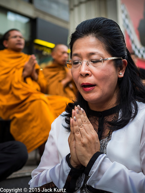 24 AUGUST 2015 - BANGKOK, THAILAND: A woman prays near Buddhist monks presiding over a memorial service for victims of the Erawan Shrine bombing. One week after the a bomb at the Erawan Shrine in the center of Bangkok killed dozens and hospitalized scores of people, police have not made any arrests. Police bomb sniffing dogs have been deployed to malls and markets around Bangkok. There was a large memorial service sponsored by businesses close the bomb site Monday evening.     PHOTO BY JACK KURTZ