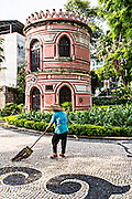 A sweeper cleans the park along the Association for the Handicapped building in the Jardim do Sao Francisco or Sao Francisco Garden in Macau.