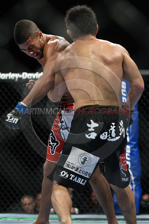 "BIRMINGHAM, ENGLAND, NOVEMBER 5, 2012: Jason Young (facing) soaks up a punch from Michihiro Omigawa during ""UFC 138: Munoz vs. Leben"" inside the National Indoor Arena in Birmingham, United Kingdom"