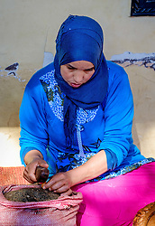 A Moroccan woman crushing Argan nuts by hand to release Argan oil at a cooperative in the Ourika Valley, Morocco, North Africa<br /> <br /> (c) Andrew Wilson | Edinburgh Elite media