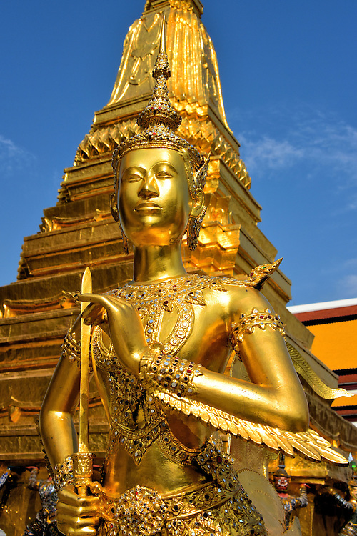 Half-man Half-bird Gold Statue at Grand Palace in Bangkok, Thailand<br /> This golden figure of a half-man, half-bird is called a Kinnara.  It originally comes from Hindu mythology but has been adapted in Thailand.  The creature, which can fly between the mystical and human worlds, marries a Kinnaris.  Their love is everlasting and their life is one of perpetual pleasure.  This statue is at Wat Phra Kaew in the Grand Palace.