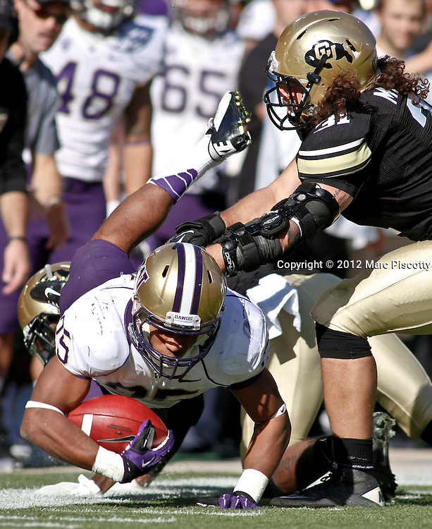 SHOT 11/17/12 1:16:23 PM - Washington's Bishop Sankey #25 dives forward for extra yardage in front of Colorado's Jon Major #31 during their Pac-12 regular season game at Folsom Field in Boulder, Co. Washington won the game 38-3. (Photo by Marc Piscotty / © 2012)