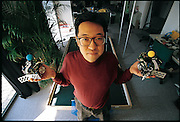In a spanking new, richly-appointed research center above a busy shopping street in Tokyo's stylish Harajuku district, Hiroaki Kitano shows off his robot soccer team. In addition to Kitano's humanoid-robot work at Kitano Symbiotic Systems Project, a five-year, government-funded ERATO project, Kitano is the founder and chair of Robot World Cup Soccer (RoboCup), an annual soccer competition for robots. There are four classes of contestants: small, medium, simulated, and dog (using Sony's programmable robot dogs). Kitano's small-class RoboCup team consists of five autonomous robots, which kick a golf ball around a field about the size of a ping-pong table. An overhead video camera feeds information about the location of the players to remote computers, which use the data to control the robots' offensive and defensive moves. Japan. From the book Robo sapiens: Evolution of a New Species, page 213 bottom.