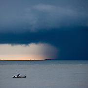 Fisherman paddling in front of large storm clouds and rain,  Belize