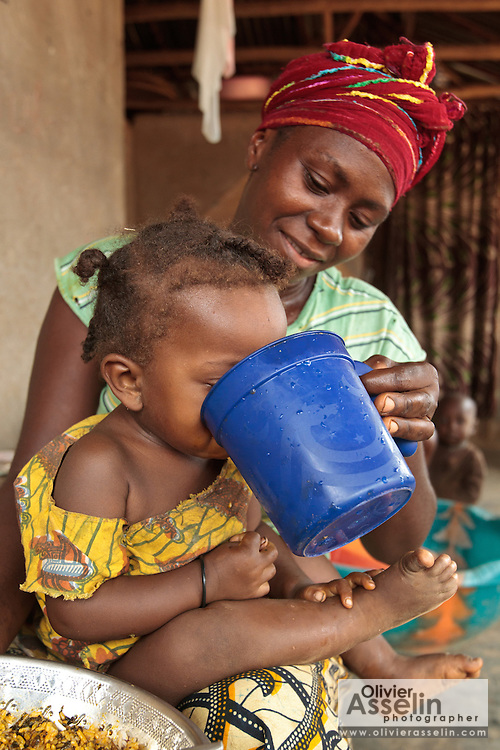 Jenneh Johnson, 31, gives water to drink to her daughter Jusu, 2, at home in the village of Julijuah, Bomi county, Liberia on Tuesday April 3, 2012. Jenneh has been receiving 2050 Liberian dollars (approx. 28 USD) per month since April 2010 through a UNICEF-sponsored social cash transfer programme. She says the money has allowed her to renovate the roof of her home, and send all her children to school. Before joining the programme only two of her children attended school.